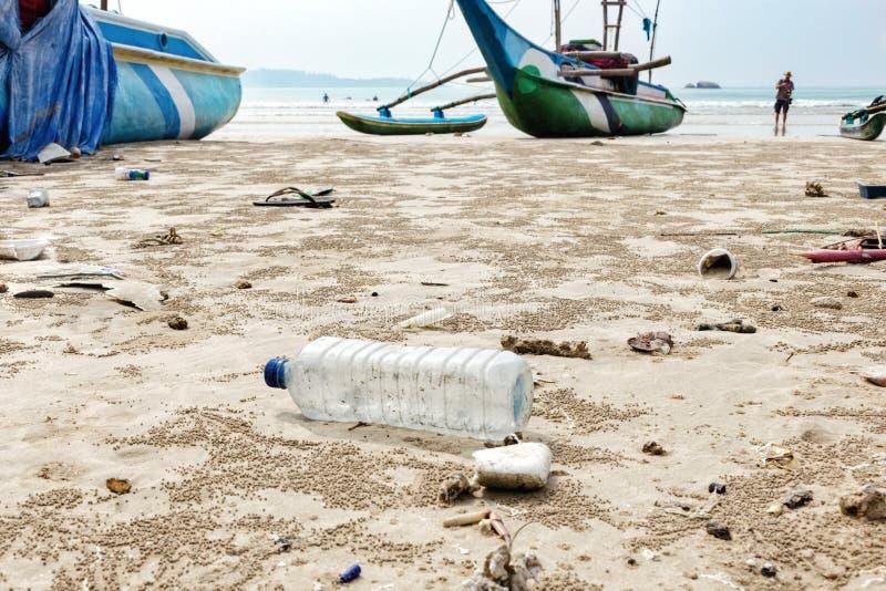 O fim acima da garrafa plástica usada vazia e de outro desperdício jogado para fora na praia do mar no fundo é barcos de pesca fotos de stock royalty free