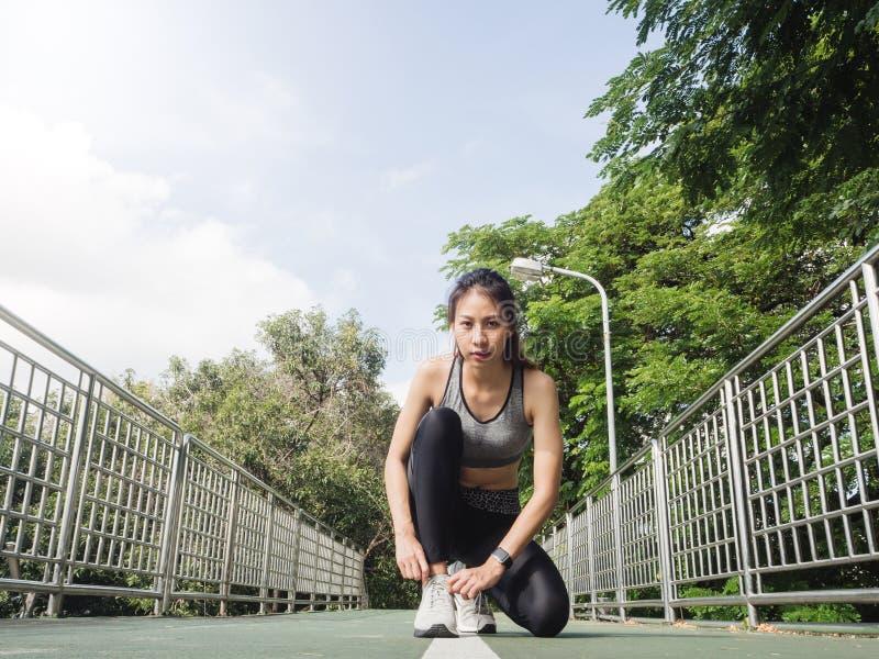 O fim acima da jovem mulher ata acima sua sapata pronta para malhar no exercício no parque com luz do sol clara morna na manhã foto de stock