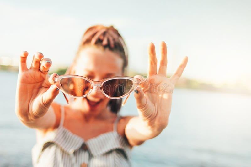 O fim acima da jovem mulher despreocupada feliz do retrato com as tranças africanas nos óculos de sol aprecia a vida na praia, te foto de stock