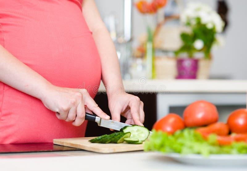 O fim acima da mulher gravida com a faca na cozinha corta o pepino foto de stock