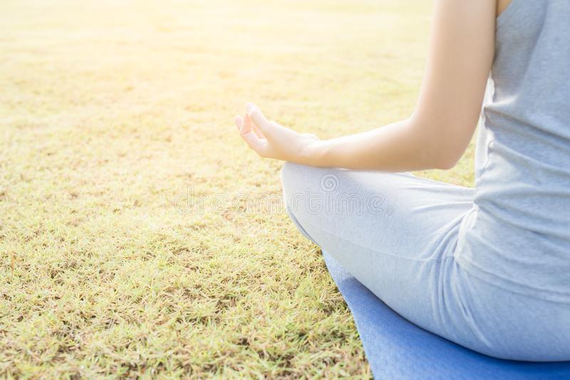 O fim acima da mulher da mão faz a ioga, menina asiática que faz a ioga no jardim com foto de stock royalty free