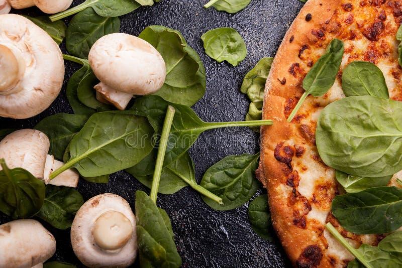 O fim acima da vista superior da pizza coberta com os espinafres sae ao lado de m fotos de stock
