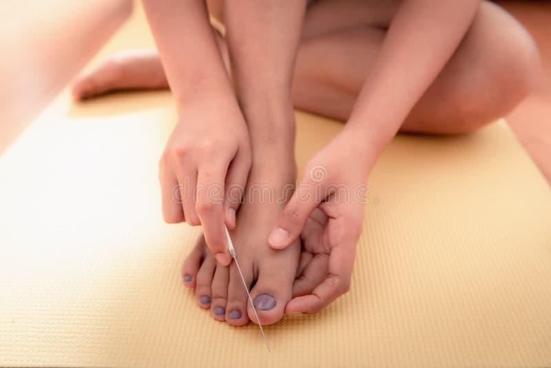 O fim acima das mãos da mulher está usando um arquivo de prego com seus pés fotografia de stock royalty free