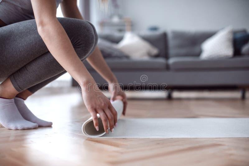 O fim acima das mãos da mulher que desenrolam a esteira está preparando-se para o exercício da aptidão em casa fotografia de stock