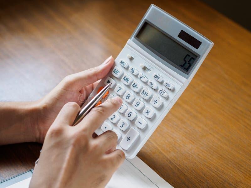 O fim acima das mãos do ` s do homem está usando a calculadora no desktop de madeira B imagem de stock royalty free