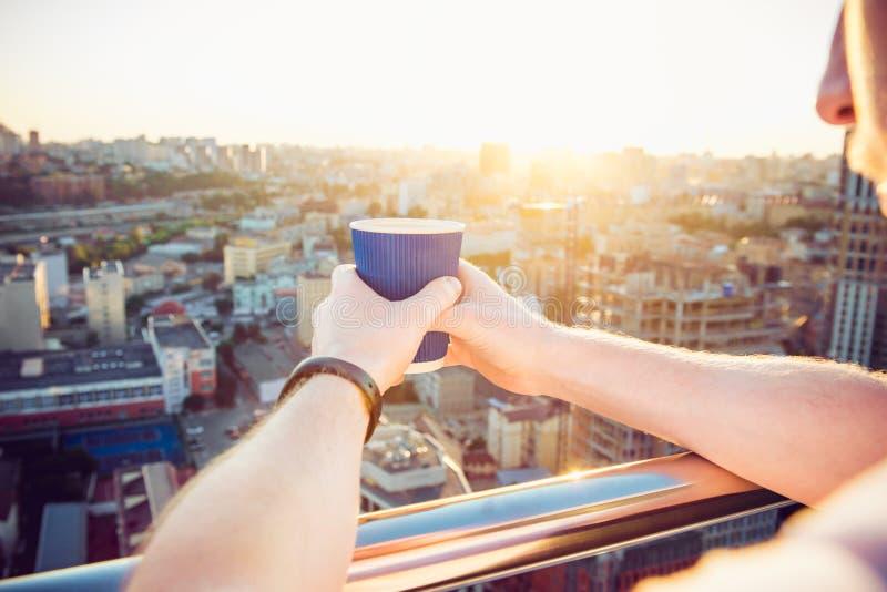 O fim acima de guardar das mãos do ` s do homem leva embora o copo de papel com bebida quente da manhã - café ou chá com vista in foto de stock