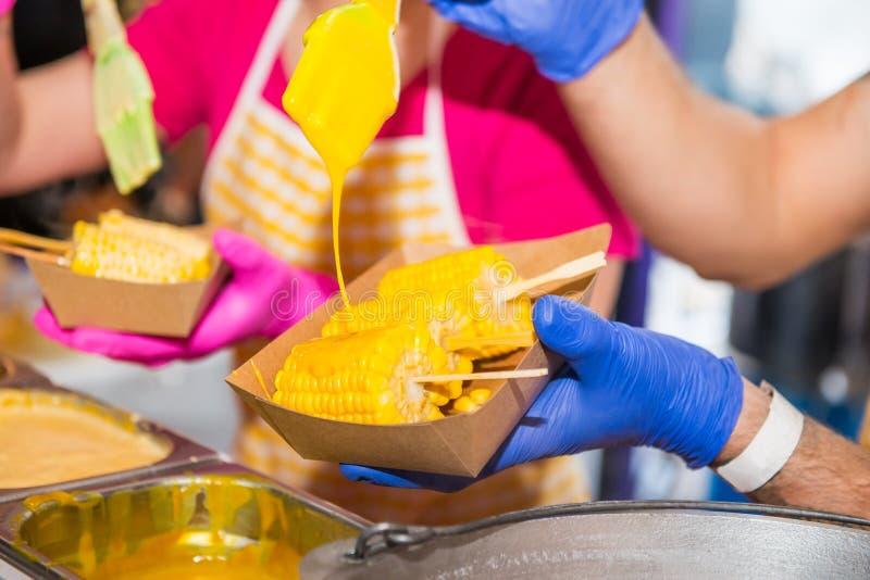 O fim acima de guardar masculino das mãos do vendedor leva embora o recipiente de alimento com milho doce cozinhado e derramament fotografia de stock