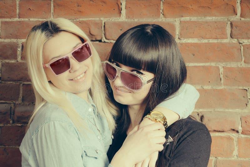 O fim acima de um retrato da forma de dois abraços das meninas e divertimentos ter junto, vestindo óculos de sol à moda, o melhor fotografia de stock royalty free