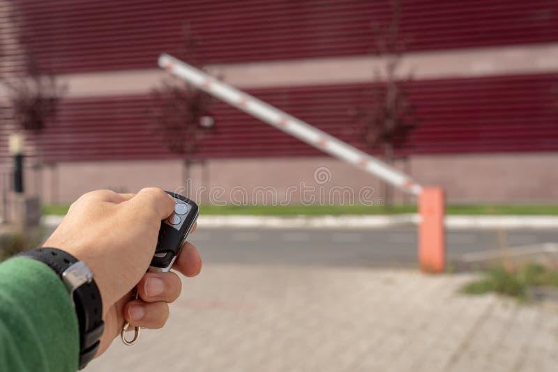 O fim acima de uma mão masculina com keychain de uma barreira abre a viagem, controlo a distância imagens de stock