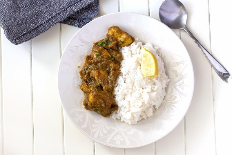O fim acima do caril e do limão indianos tradicionais da galinha da manteiga serviu com a placa branca fervida do arroz Vista sup imagens de stock
