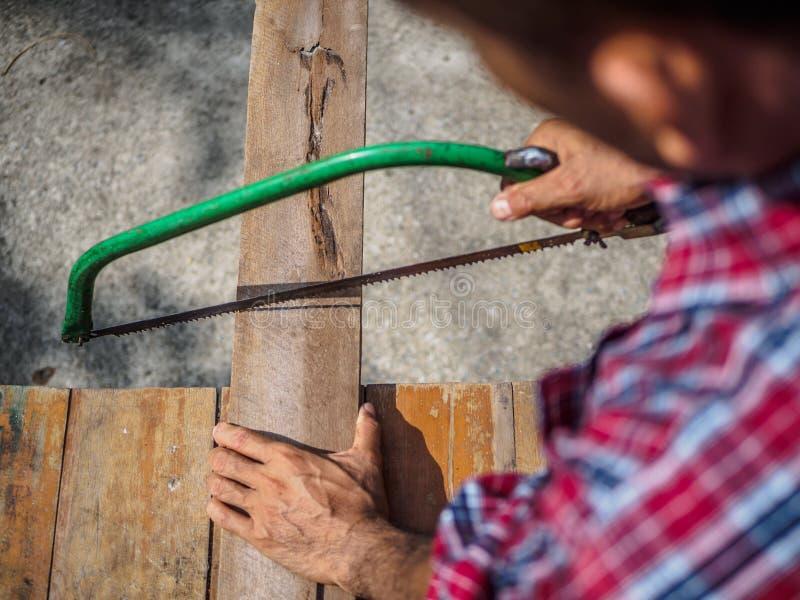 O fim acima do carpinteiro que vê uma placa com uma madeira da mão considerou Profe fotografia de stock royalty free