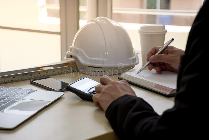 O fim acima do coordenador de projeto civil está fazendo cálculos da análise estrutural usando uma calculadora científica fotografia de stock