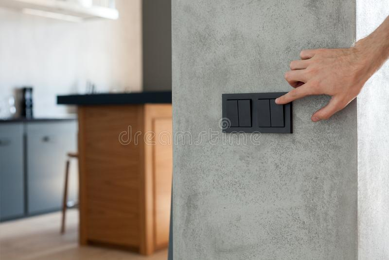 O fim acima do dedo está girando de ligar/desligar no interruptor da luz Copie o espaço fotografia de stock