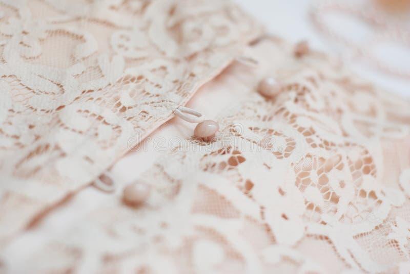 O fim acima do detalhe do fragmento de mulheres do laço veste-se com fundo da textura da forma dos botões imagens de stock royalty free