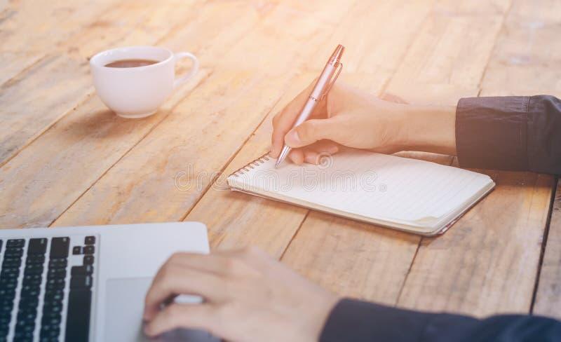 O fim acima do homem de negócios escreve o caderno e portátil da utilização na aba de madeira imagem de stock