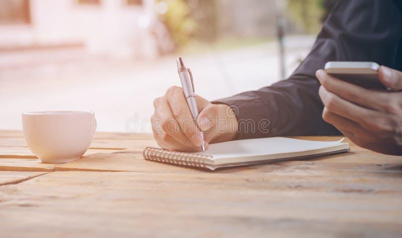 O fim acima do homem de negócios escreve o caderno e telefone celular da utilização foto de stock royalty free