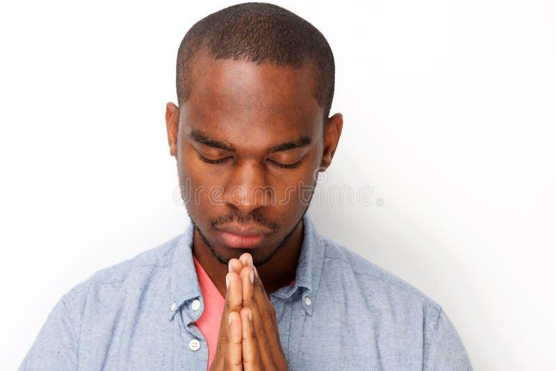 O fim acima do homem negro novo que reza com mãos abraça junto fotografia de stock
