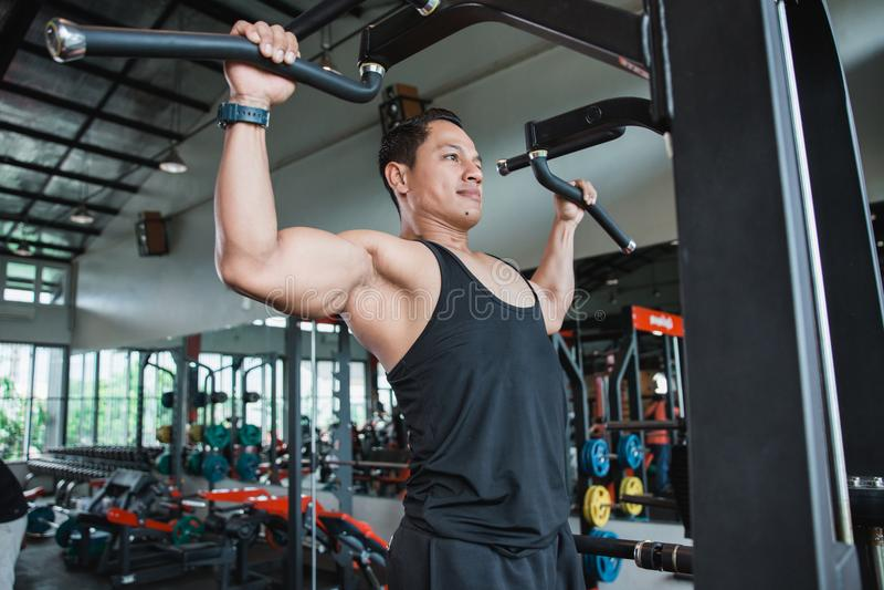 O fim acima do homem que exercita e que faz a tração levanta imagens de stock