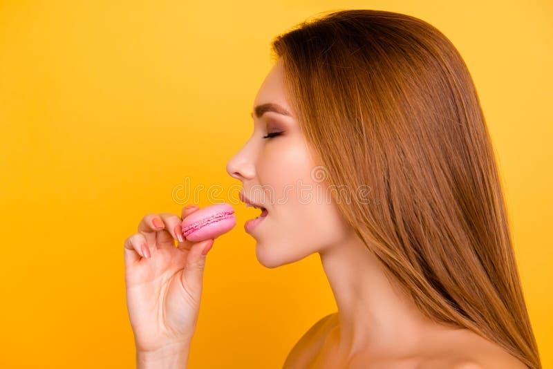 O fim acima do perfil da mulher encantador quer morder macar cor-de-rosa saboroso fotos de stock royalty free