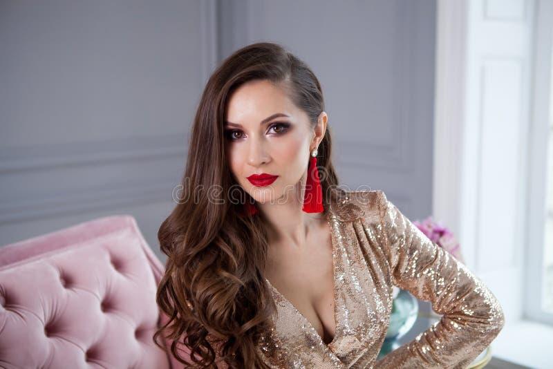 O fim acima do retrato da escada da forma da menina bonita no vestido de partido de brilho do ouro à moda senta-se em um sofá cor imagem de stock