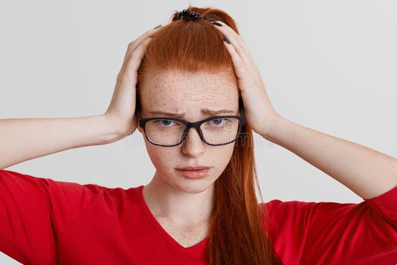 O fim acima do retrato de fêmea freckled emocional frustrante mantém as mãos na cabeça, veste espetáculos quadrados, tem a dor de fotografia de stock