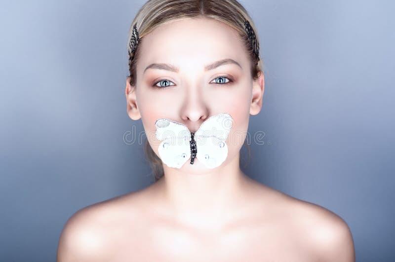 O fim acima do retrato de um modelo de olhos azuis bonito novo com pele perfeita e o nude compõem guardar uma borboleta de papel  fotografia de stock