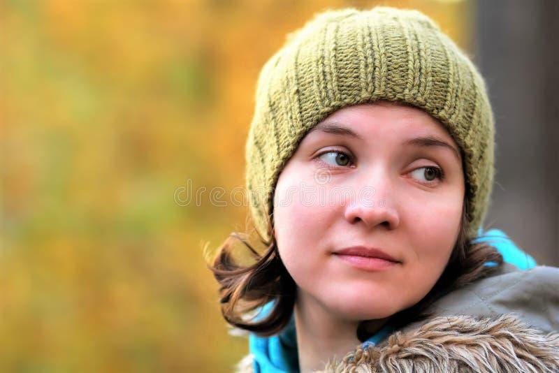 O fim acima do retrato de uma jovem mulher bonita em uma caminhada no parque do outono na cor verde-oliva feito à mão fez malha o imagens de stock