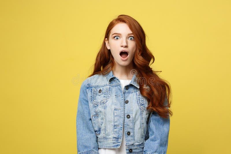 O fim acima do retrato surpreende a menina atrativa bonita nova do redhair que choca-se com algo Isolado no amarelo brilhante fotografia de stock