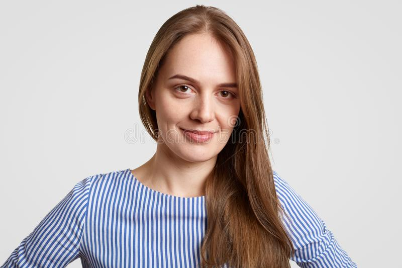 O fim acima do tiro da mulher de cabelo escura bonita deleitada olha diretamente na câmera, mostra a beleza natural, sorri gladfu foto de stock royalty free