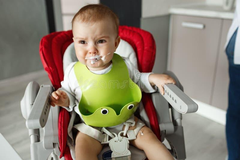O fim acima do um ano pequenos infelizes do filho no babador verde que grita e que grita na cadeira para bebês após a mamã fê-lo  foto de stock