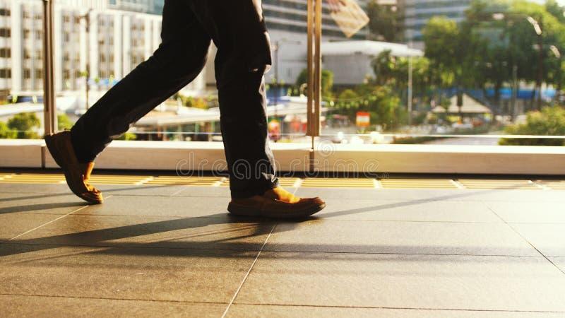 O fim acima dos pés do ` s do homem anda no cruzamento pedestre em um dia ocupado no centro da cidade em um dia ensolarado na est fotos de stock