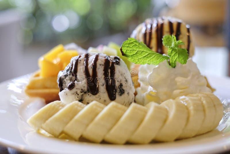 o fim acima dos waffles serviu com frutos misturados, banana cortada, gelado e cobriu com molho de chocolate imagens de stock