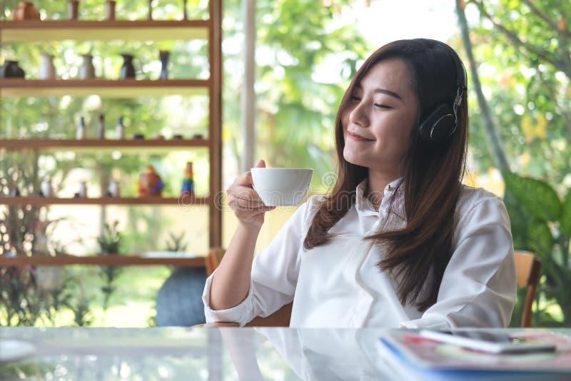 O fim asiático da mulher seus olhos e escuta a música com fones de ouvido ao beber o café com sentimento feliz e relaxa no café c fotografia de stock