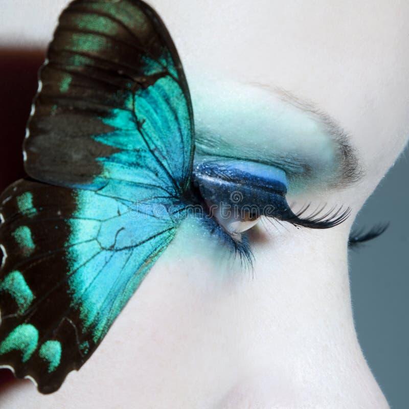 O fim bonito do olho da mulher acima com borboleta voa fotografia de stock
