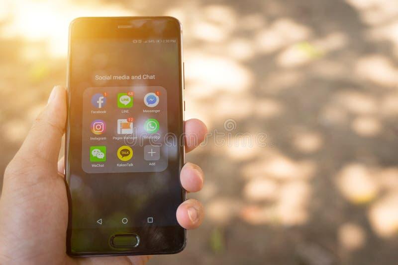 O fim da mão do ` s da pessoa mantém o telefone esperto com ícones sociais da aplicação dos meios mostra na tela fotos de stock royalty free