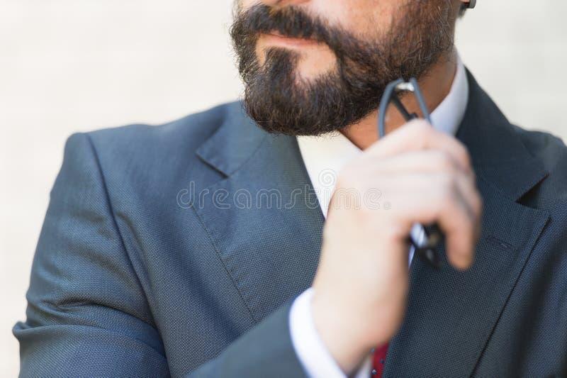 O fim da mão farpada do queixo mantém vidros do homem de negócios no terno e no laço vermelho O homem de negócios pensa sobre com fotos de stock