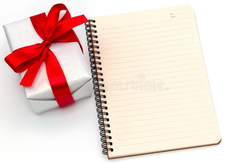 O fim da vista superior objeta acima a fita vermelha e o caderno do laço branco da caixa de presente isolados no Feliz Natal bran imagens de stock
