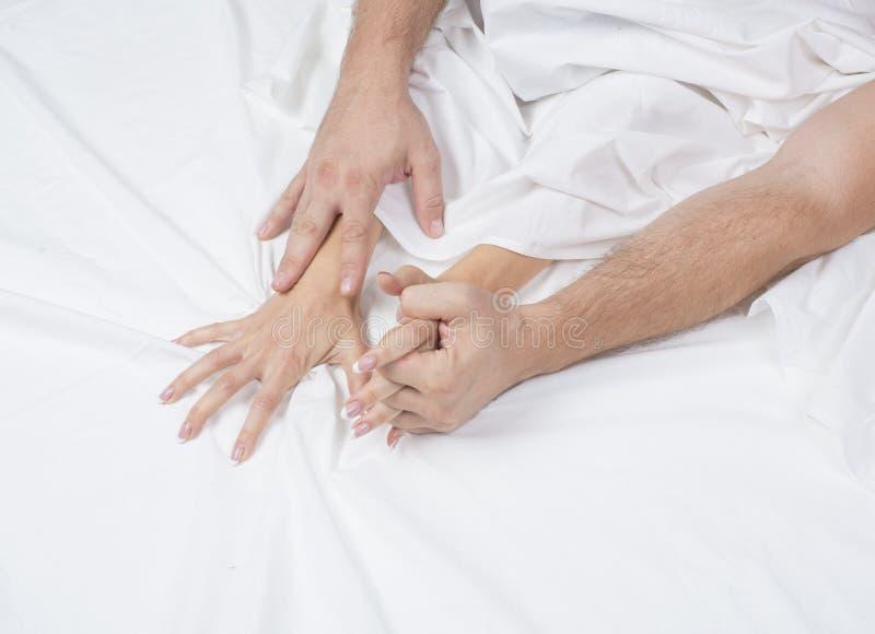 O fim de pares apaixonado mantém as mãos durante a fatura do amor intenso no quarto, amantes aprecia o sexo quente na folha branc imagens de stock