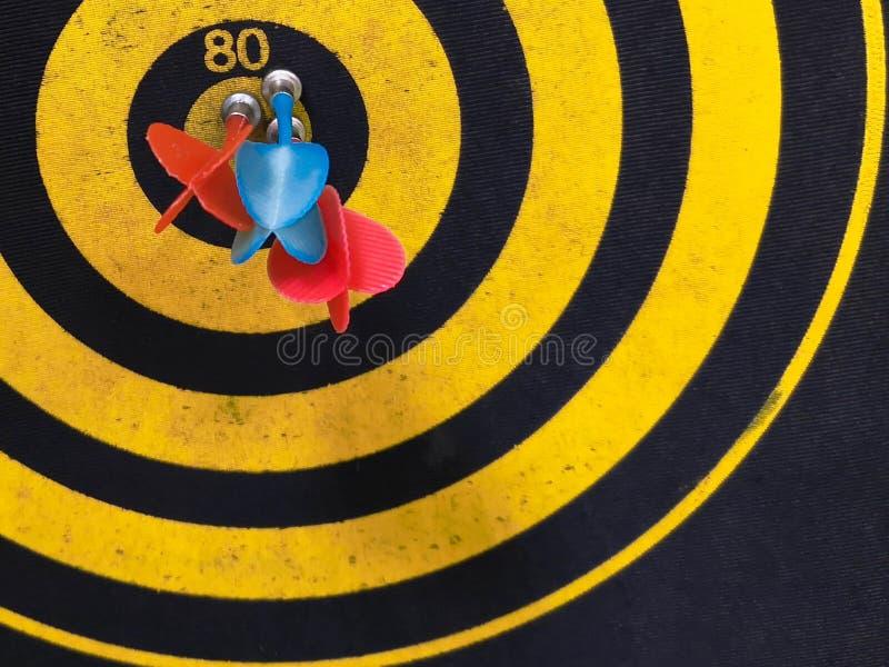 O fim disparou acima de uma placa de dardo Seta dos dardos que falta o alvo em uma placa de dardo durante o jogo Amarelo dos dard fotografia de stock royalty free