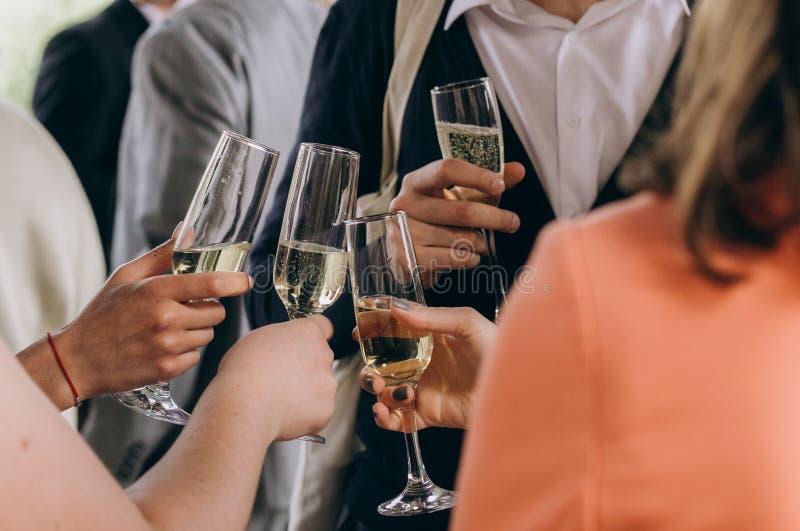 O fim do champanhe dos vidros dos amigos da empresa entrega o partido fotografia de stock