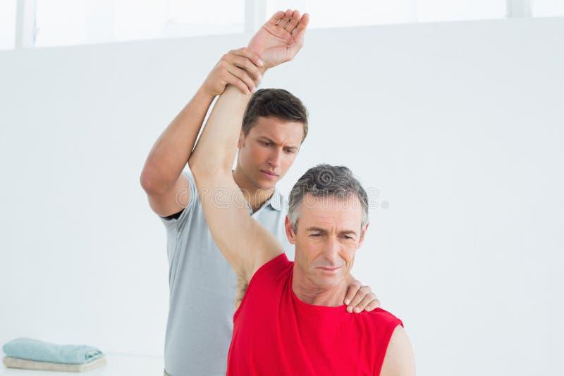 O fisioterapeuta masculino que estica um maduro equipa o braço foto de stock