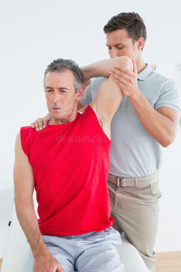 O fisioterapeuta masculino que estica um maduro equipa o braço imagem de stock royalty free