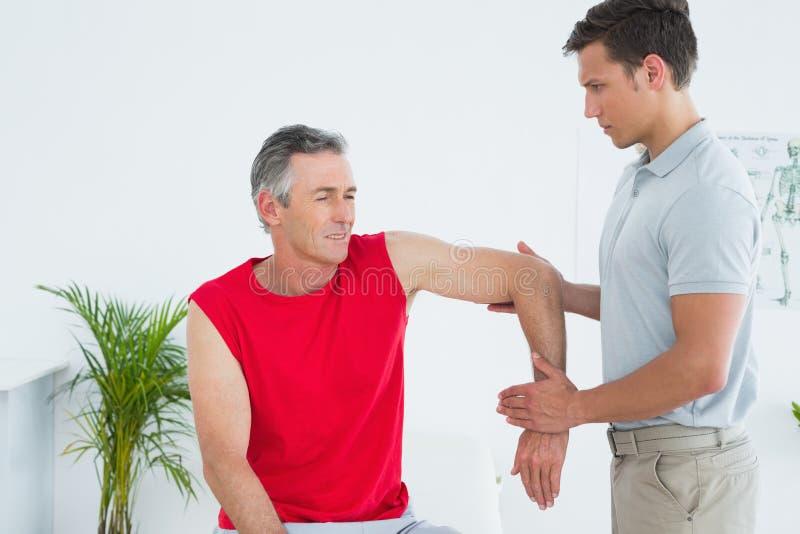 O fisioterapeuta masculino que estica um maduro equipa o braço fotografia de stock