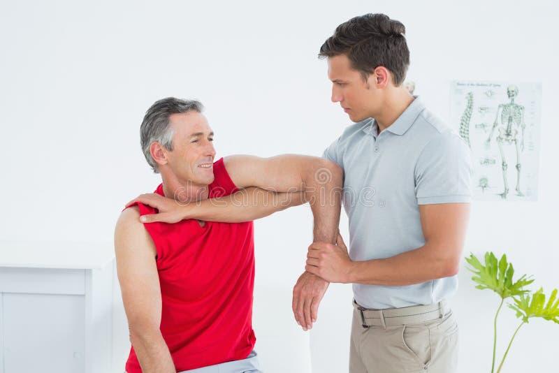 O fisioterapeuta masculino que estica um maduro equipa o braço imagens de stock
