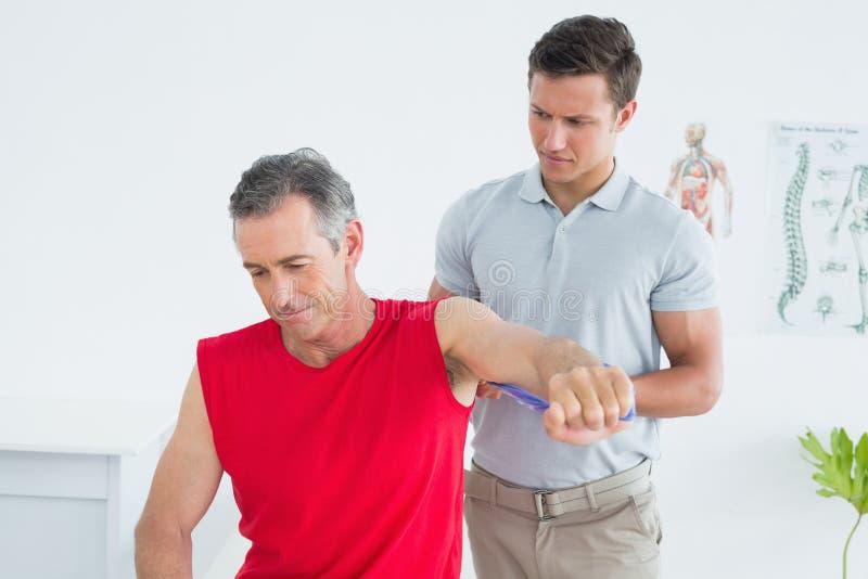 O fisioterapeuta masculino que examina um maduro equipa o braço foto de stock