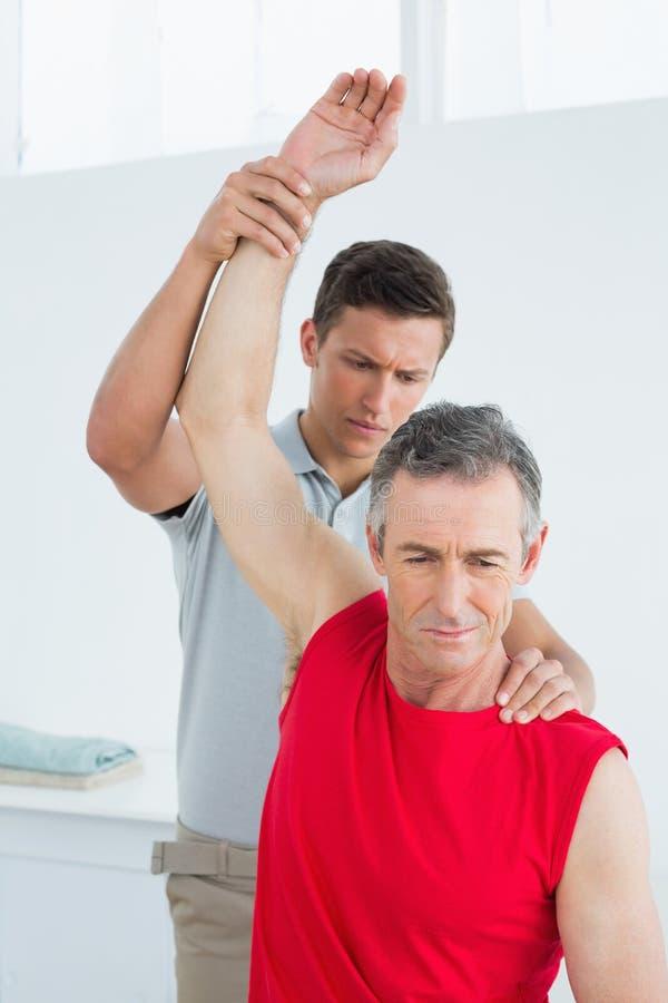 O fisioterapeuta que estica um maduro equipa o braço imagens de stock