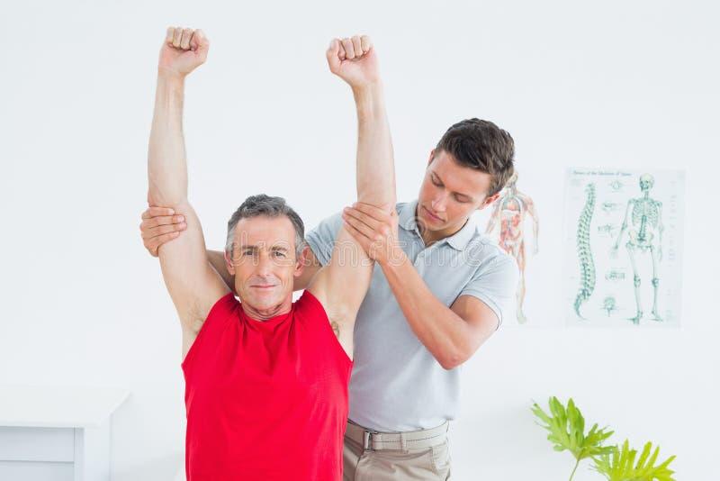 O fisioterapeuta que estica um maduro equipa os braços foto de stock