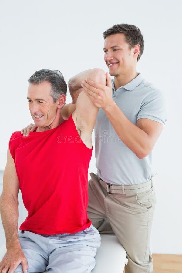 O fisioterapeuta que estica um sorriso maduro equipa o braço foto de stock
