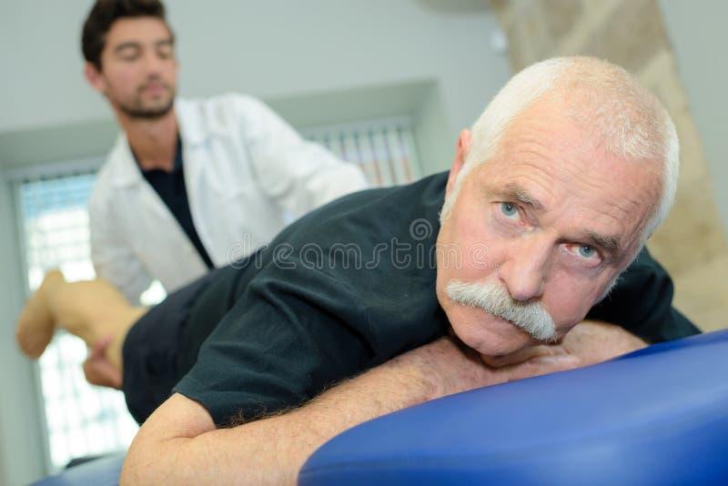 O fisioterapeuta que faz o ombro exercita com o paciente masculino idoso imagem de stock