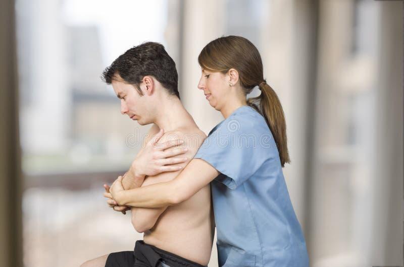 O fisioterapeuta, quiroprático está fazendo uma manipulação dorsal global para um paciente masculino foto de stock